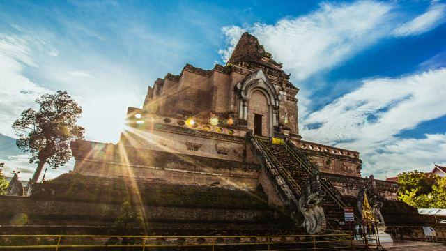 契迪龙寺是清迈很有名的寺庙,而且占地面积大,很值得好好仔细逛逛。寺庙里有寺庙还有佛塔。 1、先介绍寺庙:庙的入口很常见的双龙守门,进寺庙是有服装要求的,穿短裙的我乖乖加上了寺院提供的外套,庙里的窗户很漂亮了,已经不是简单的窗户,是一幅艺术品。庙里有个金人,原身是当地一位贵族,帮忙解决了地方的内讧,深受当地人们爱戴,所以供奉在庙里受民众敬拜。和中国人喜欢往池子和佛像扔钱币一样原理,泰国人喜欢用金箔贴佛像祈福。 2、介绍庙里的佛塔,寺内高大的兰纳风格佛塔建于1441年,毁于16世纪的一次地震,但依然是城内最宏