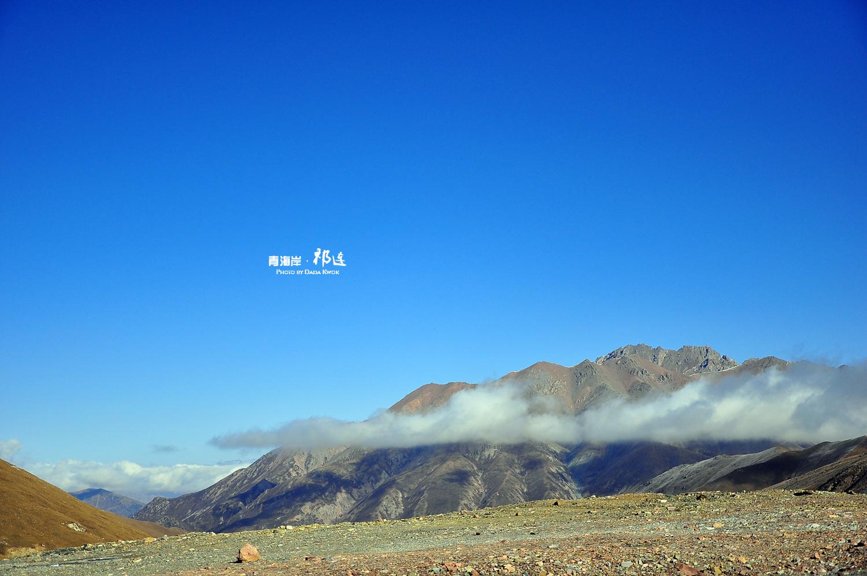 汽车绕着盘山公路行到了海拔4120米的大冬树山垭口,风中的经幡与雪中